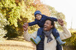 Autumn Walk With Father Carrying Son On Shoulders