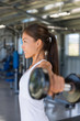 Gym woman fitness training arms lifting free weights. Dumbbell lateral raise shoulder workout.