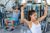 Shoulder pull down machine. Fitness girl training chest muscles at gym.