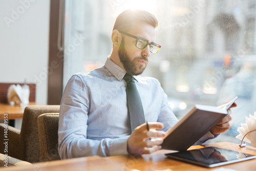 Serious businessman reading his notes while sitting in cafe
