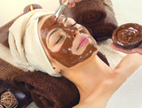 Chocolate Spa. Beautiful young woman relaxing in spa salon, applying chocolate face mask