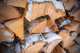 Firewood covered with snow, background
