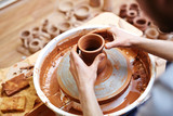 Young master making clay jug in pottery-wheel