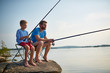 Portrait of handsome bearded father fishing with son sitting on rock in still lake with fishing rods and gear on sunny summer day