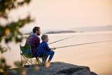Side view portrait of father and son sitting together on rocks fishing with rods in calm lake waters with landscape of setting sun, both wearing checkered shirts, shot from behind tree - 140475365