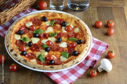 Hot tasty pizza with pepperoni, mozzarella, cherry tomatoes and basil, served on a wooden table for a dinner in italian restaurant. Pizza from wooden oven. Italy food concept.
