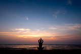 Young healthy man practicing yoga on the beach at sunset