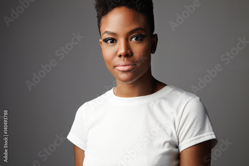 portrait of black woman with short haircut with drama makeup eyes in grey background