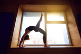 Woman doing yoga bridge on the background window. Exercising at home.