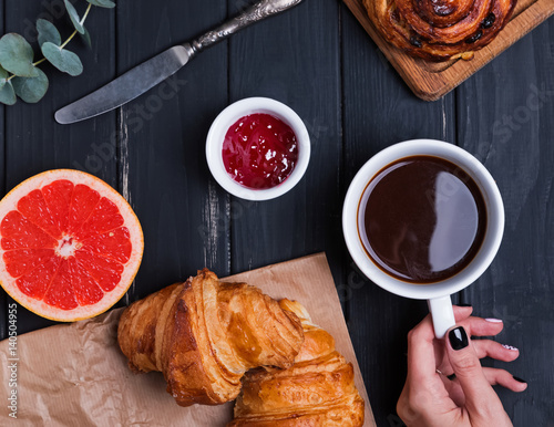 Delicious breakfast with croissants and woman's hand holding cupof coffee on the black table,