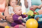 Junge Frauen in Mutter-Kind-Gymnastik spielen mit ihren Babys