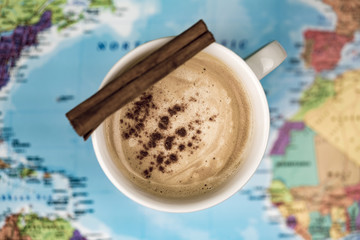 Cup of coffee with quill of cinnamon over world map blurred in background
