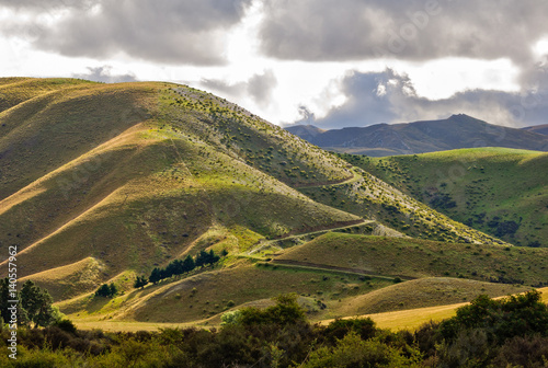Light and shadow on the rolling hills at Lindis Pass in Central Otago on the Sou Poster