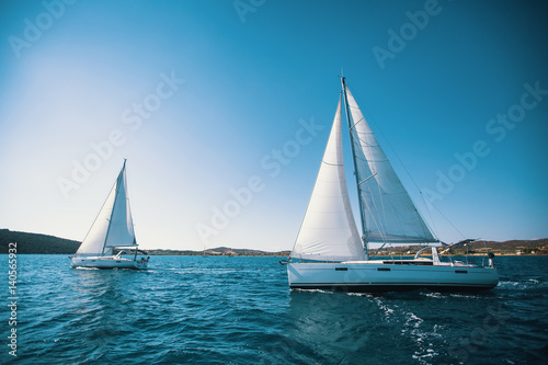 Fotobehang Zeilen Sailing ship yachts with white sails in the sea.