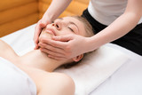 Young pretty woman enjoying face massage procedure