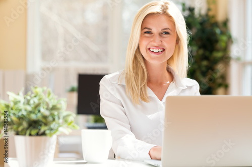 Happy young woman sitting at her desk