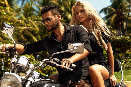 Man riding on a motorcycle with girlfriend on road.