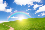 idyllic landscape of green heels, blue sky, rainbow and sun
