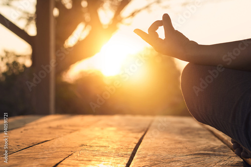 Hand of woman practicing meditation yoga on the nature at sunset - 140591721