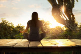 Woman practicing meditation yoga on the nature at sunset - 140593319