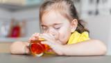 little girl drinking apple juice at the kitchen
