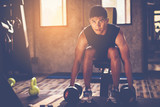 Fototapety Portrait of a male muscular bodybuilder workout with dumbbell in fitness gym.