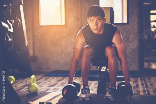 Portrait of a male muscular bodybuilder workout with dumbbell in fitness gym Poster