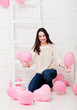 Happy beautiful young girl with pink balloons in with room.