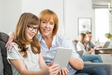 Fototapety Loving mother and daughter using tablet PC with family sitting in background at home
