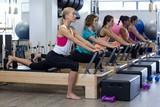 Fototapety Group of women exercising on reformer