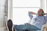 Fototapety Full-length of relaxed Middle-aged man listening to music at home