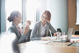Fototapety Smiling young businesswomen having lunch at table in office