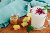 Pineapple banana milkshake with raspberry topping