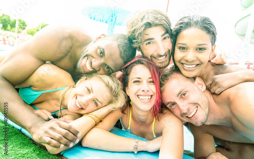 Faces of best friends taking selfie at swimming pool party - Happy youth and friendship concept with young multiracial people having fun together at summer aquapark - Bright desaturated filter