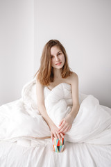 Portrait of smiling beautiful young Caucasian girl woman with long red hair sitting in bed wrapped covered with blanket, holiding cup, drinking coffee or tea, on white background.