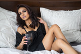 Beautiful woman relaxing in bed drinking wine