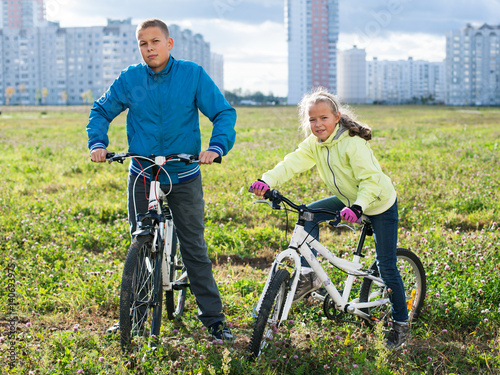 Poster Children riding their bikes on a green field in the city