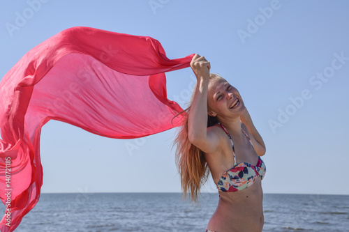 Blond girl in a bikini standing on the beach and holding a red silk handkerchief. Beautiful young woman in a colorful bikini on sea background