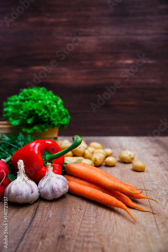Vegetables. Potatoes, carrot and red pepper. Lettuce salad and garlic. Natural organic bio food. Wooden basket on rustic table.