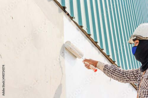 Close up of painter wear safety helmet and painting a wall with paint roller