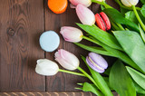 Rose-colored tulips with macarons on a wooden background