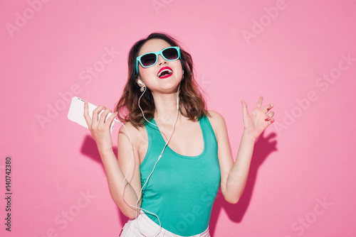Fototapeta Summer lady. Beautiful asian girl with professional makeup and stylish hairstyle singing and dancing while listening to music on pink background.