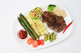 Grilled beef grilled with asparagus, zucchini, lobi, broccoli, tomato, chili and red sauce on a white plate, over white background