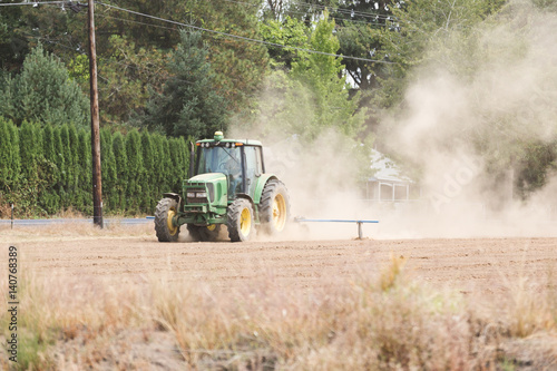 Tractor Working in a Dusty Field Poster
