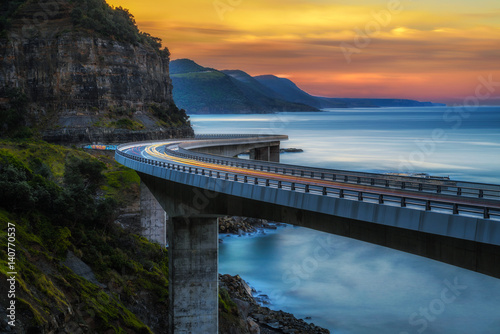 Sunset over the Sea cliff bridge along Australian Pacific ocean coast with lights of passing cars