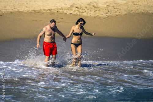 Young and attractive couple on the beach is going to swim. Sunny day, waves on water, Barcelona, Spain