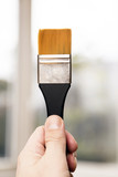 Male hand holding a flat tip paint brush