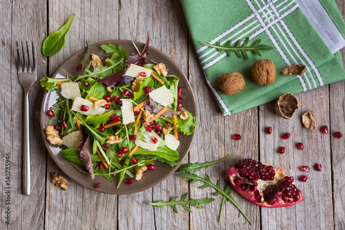 Salad with rucola and pomegranate on brown plate