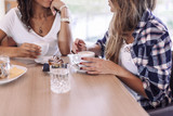 Fototapety Two young and beautiful women meet at the bar for a cappuccino and to chat