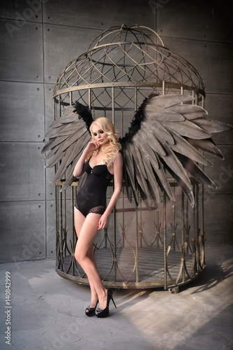 blond woman with black wings in a cage. Angel, mysticism